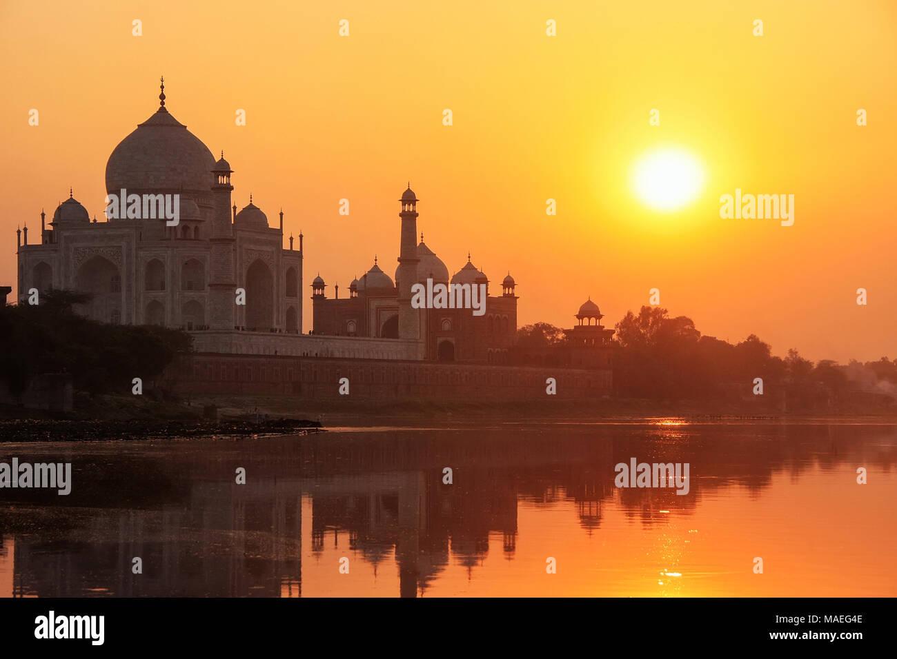 El Taj Mahal reflejado en el río Yamuna al atardecer en Agra, India. Fue encargado en 1632 por el Emperador mogol Shah Jahan para albergar la tumba de su fa Imagen De Stock