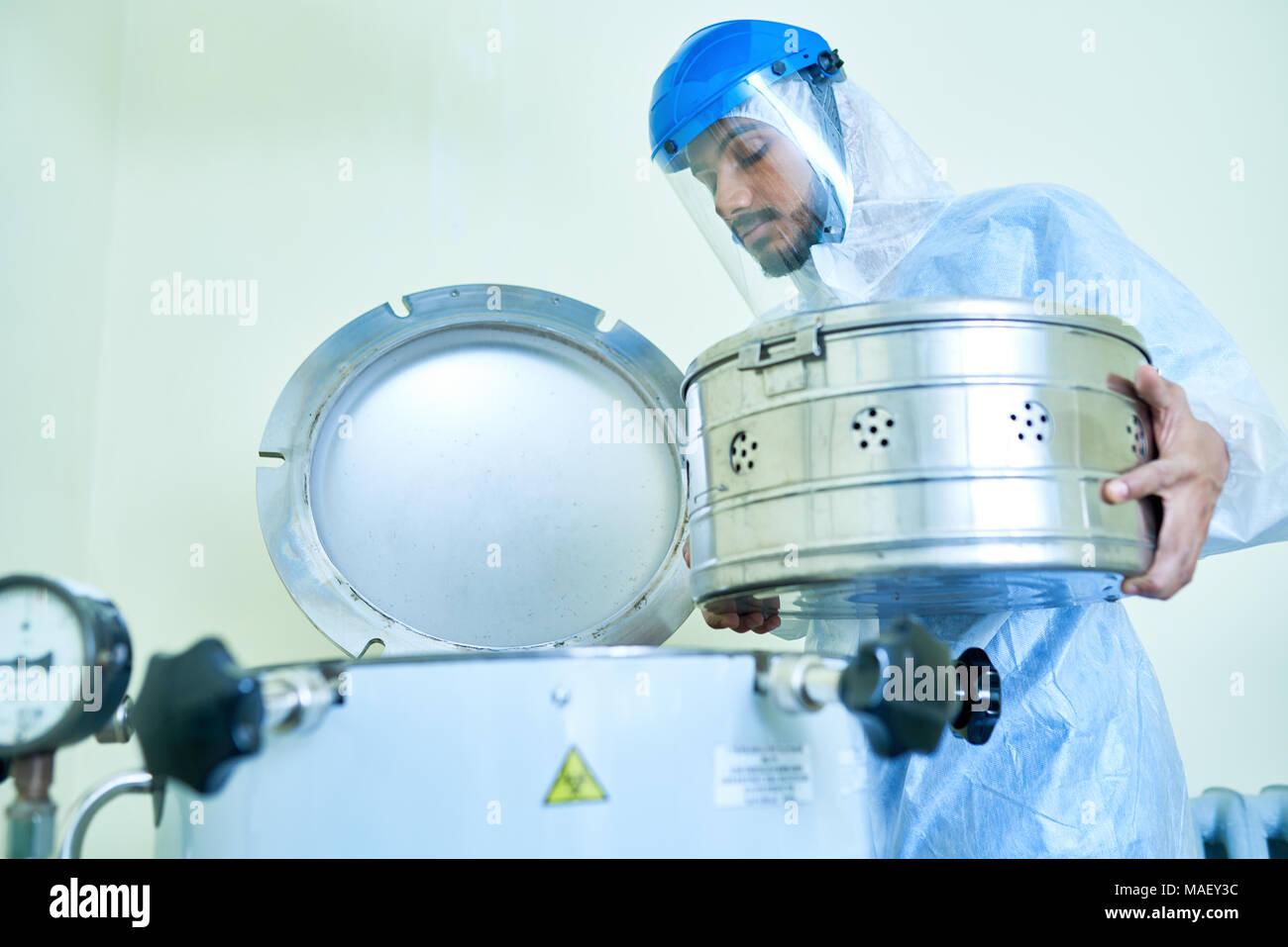 Auxiliar de laboratorio colocando el contenedor en centrífuga Imagen De Stock