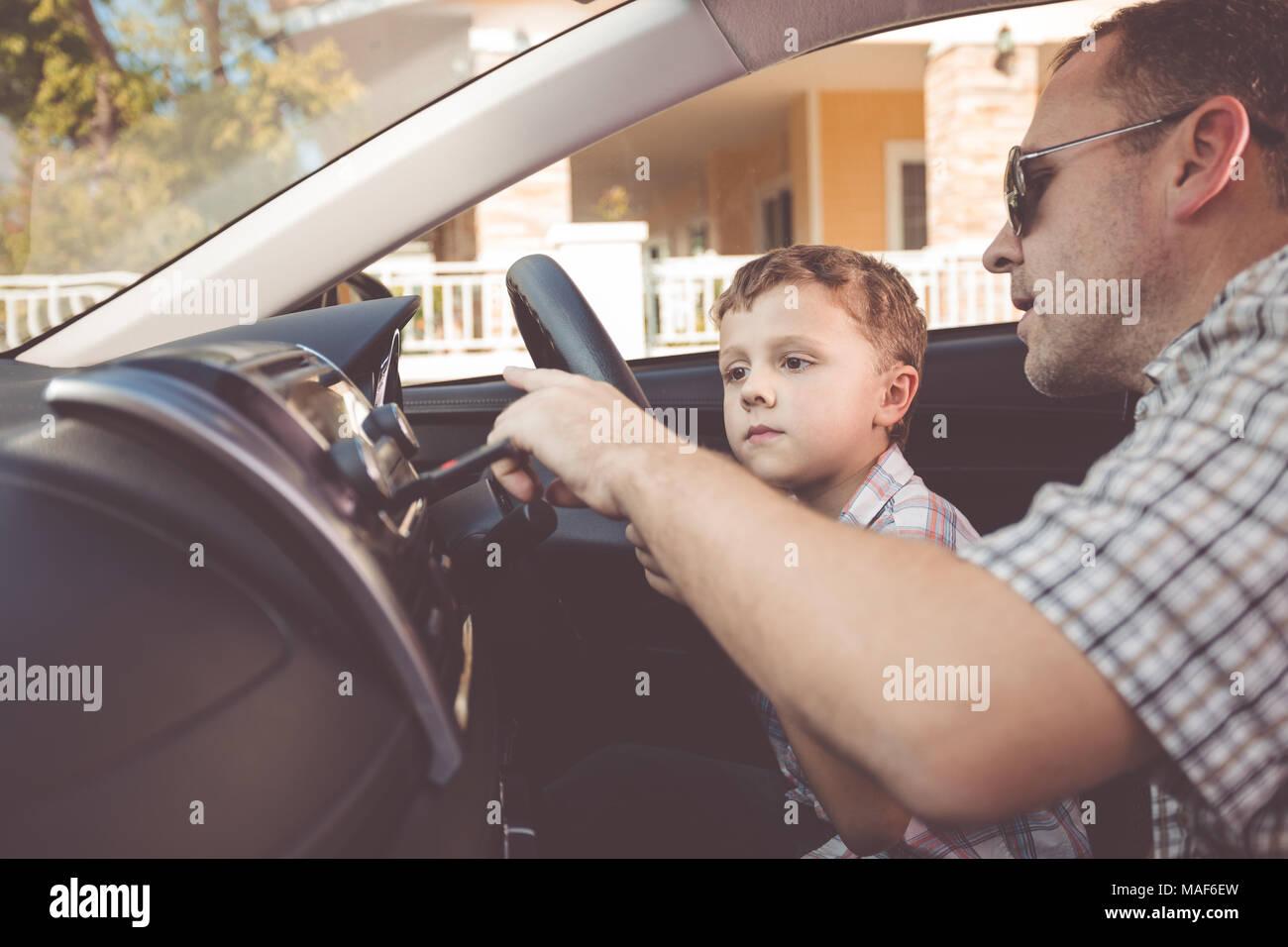 Feliz padre e hijo sentados en el coche en el día. Las personas preparándose para el viaje por carretera. Concepto de familia feliz. Imagen De Stock