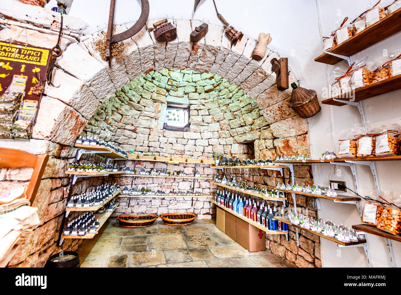 Alberobello, Italia - 10 de julio de 2015: Trullo tradicional casa con tienda de souvenir en Alberobello, Puglia. Imagen De Stock