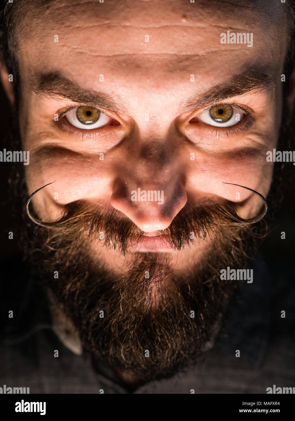 Inventor Hipster con barba y Mustages en el cuarto oscuro. Embaucador sonriente. Imagen De Stock