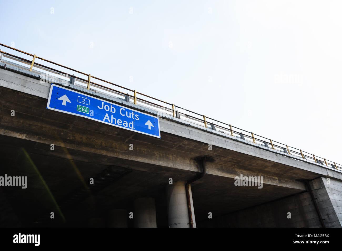 Reducciones de puestos de trabajo por delante Blue Road signo contra el cielo claro Imagen De Stock