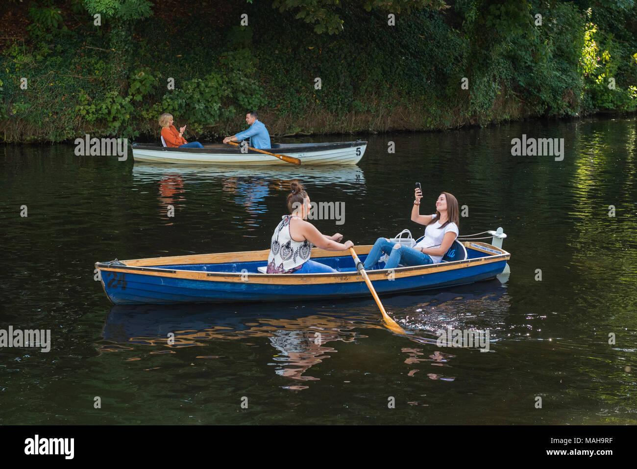 4 personas boating, relajarse y divertirse en 2 botes a remo (1 joven en barco está tomando selfie) - Río Nidd en verano, Knaresborough, Inglaterra, Reino Unido. Imagen De Stock