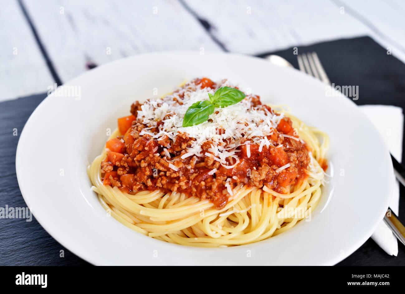 Deliciosa pasta italiana, comida, los espaguetis a la boloñesa sobre una placa blanca. Plato de pasta, comida italiana tradicional con queso parmesano, carne picada y hojas de albahaca. Imagen De Stock
