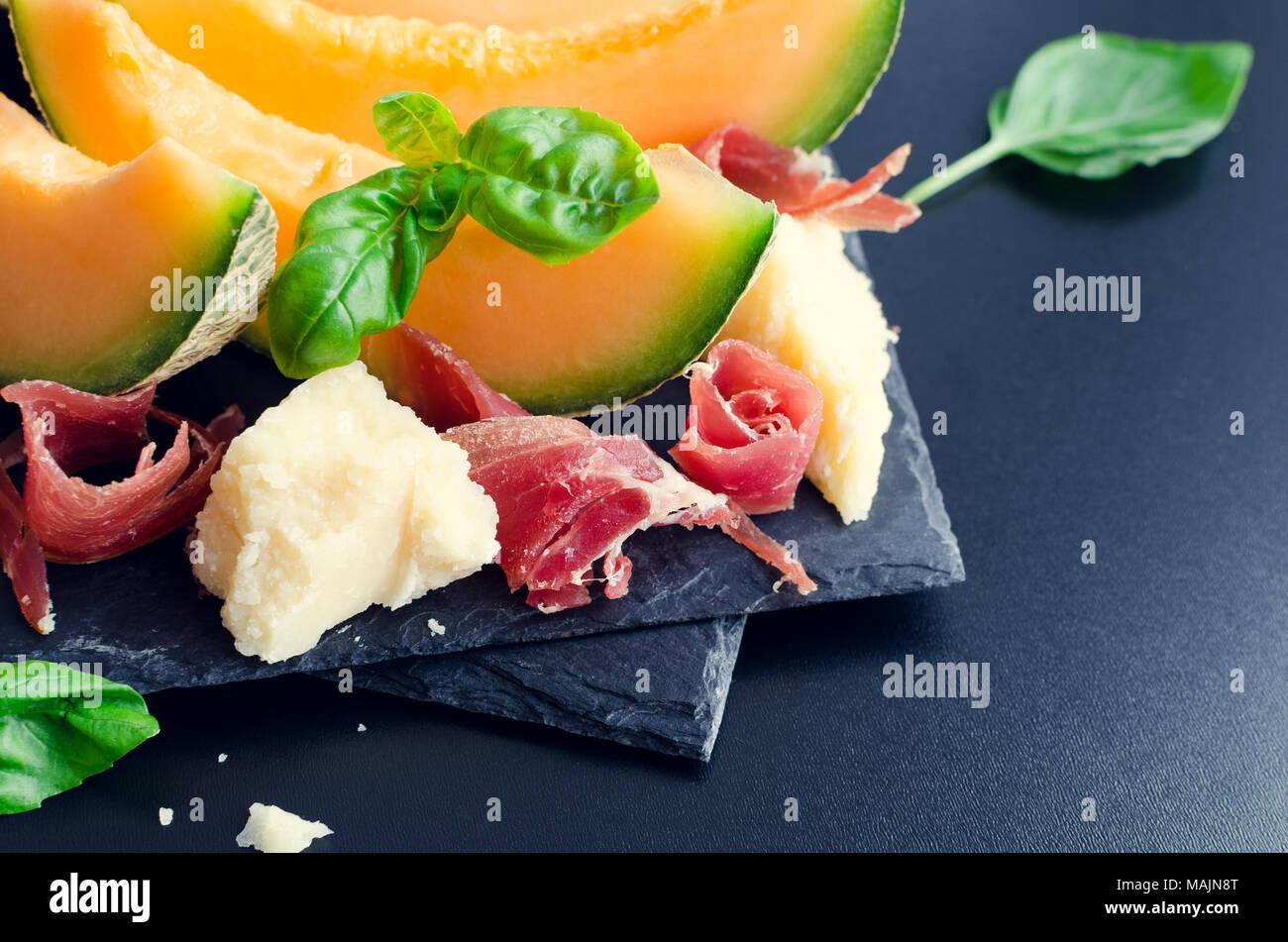 Concepto de comida italiana con melón y jamón sobre fondo oscuro. Aperitivo tradicional antipasto. El enfoque selectivo. Imagen De Stock