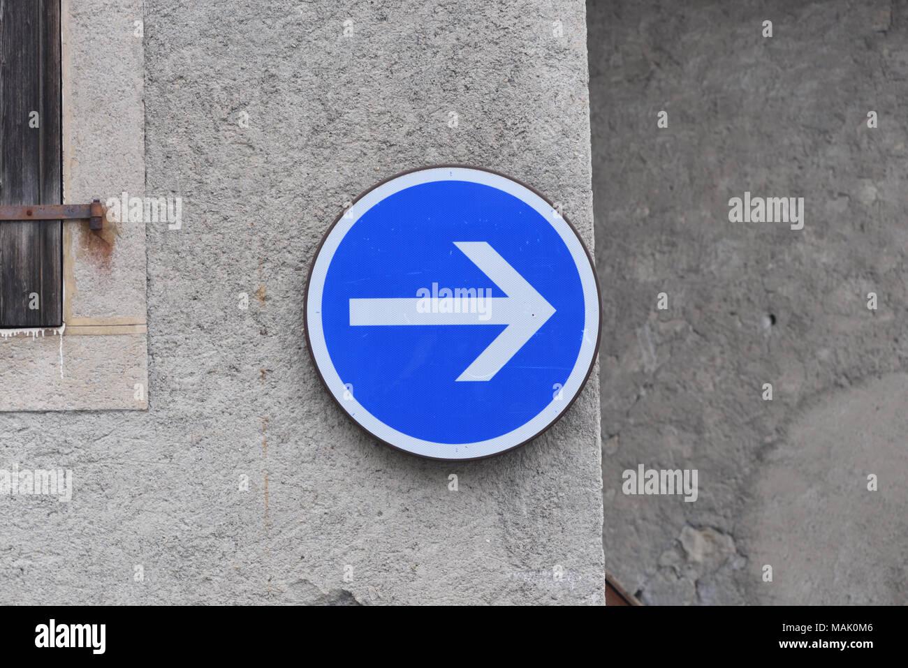Azul y blanco Dirección de tráfico firmar en la forma de una flecha en un muro de piedra. Samoens, Haute Savoie, Francia. Imagen De Stock