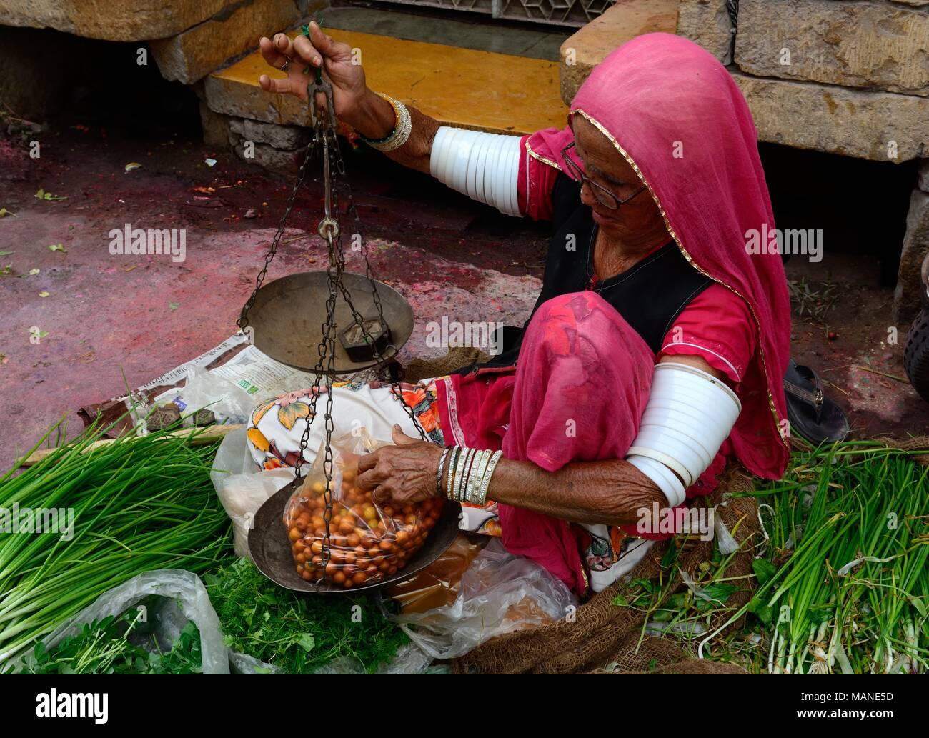 Ancianos mujer India vendiendo frutas y verduras llevaba muchos brazaletes blancos en sus brazos para alentar a la larga vida de su marido Jaisalmer India Imagen De Stock