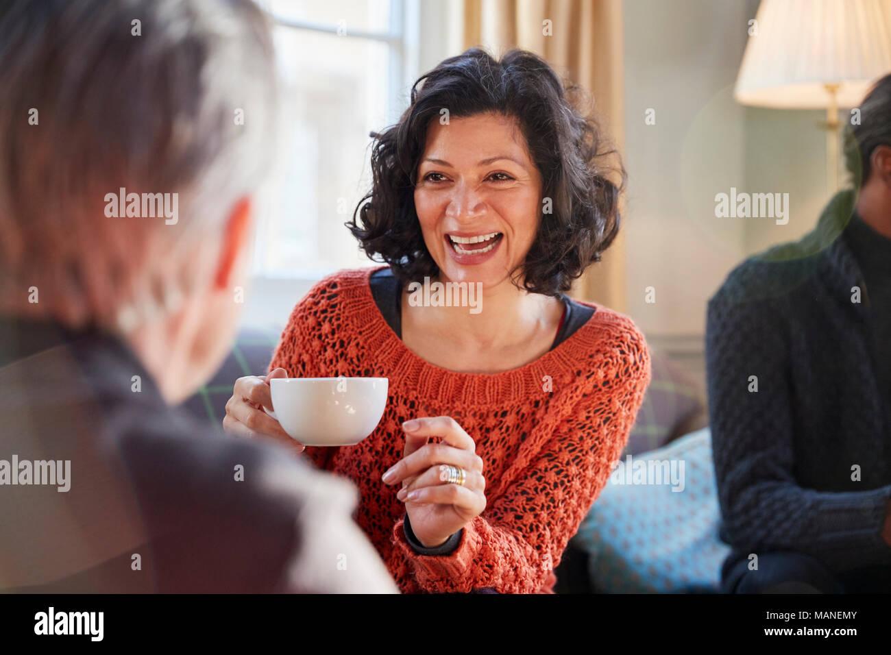 Mujer de mediana edad reunión de amigos en torno a una mesa en la cafetería. Imagen De Stock