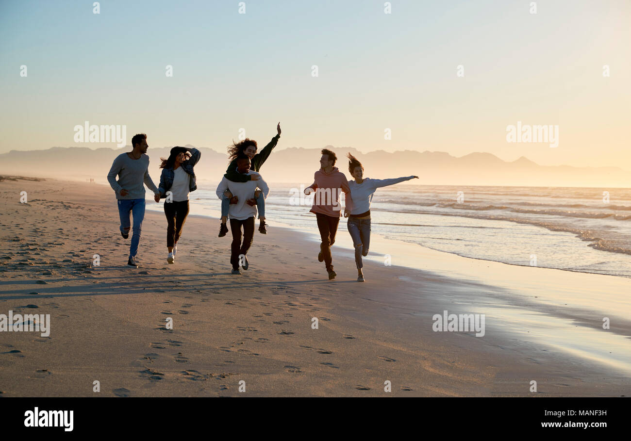 Grupo de Amigos divirtiéndose en funcionamiento a lo largo de la playa de invierno juntos Imagen De Stock