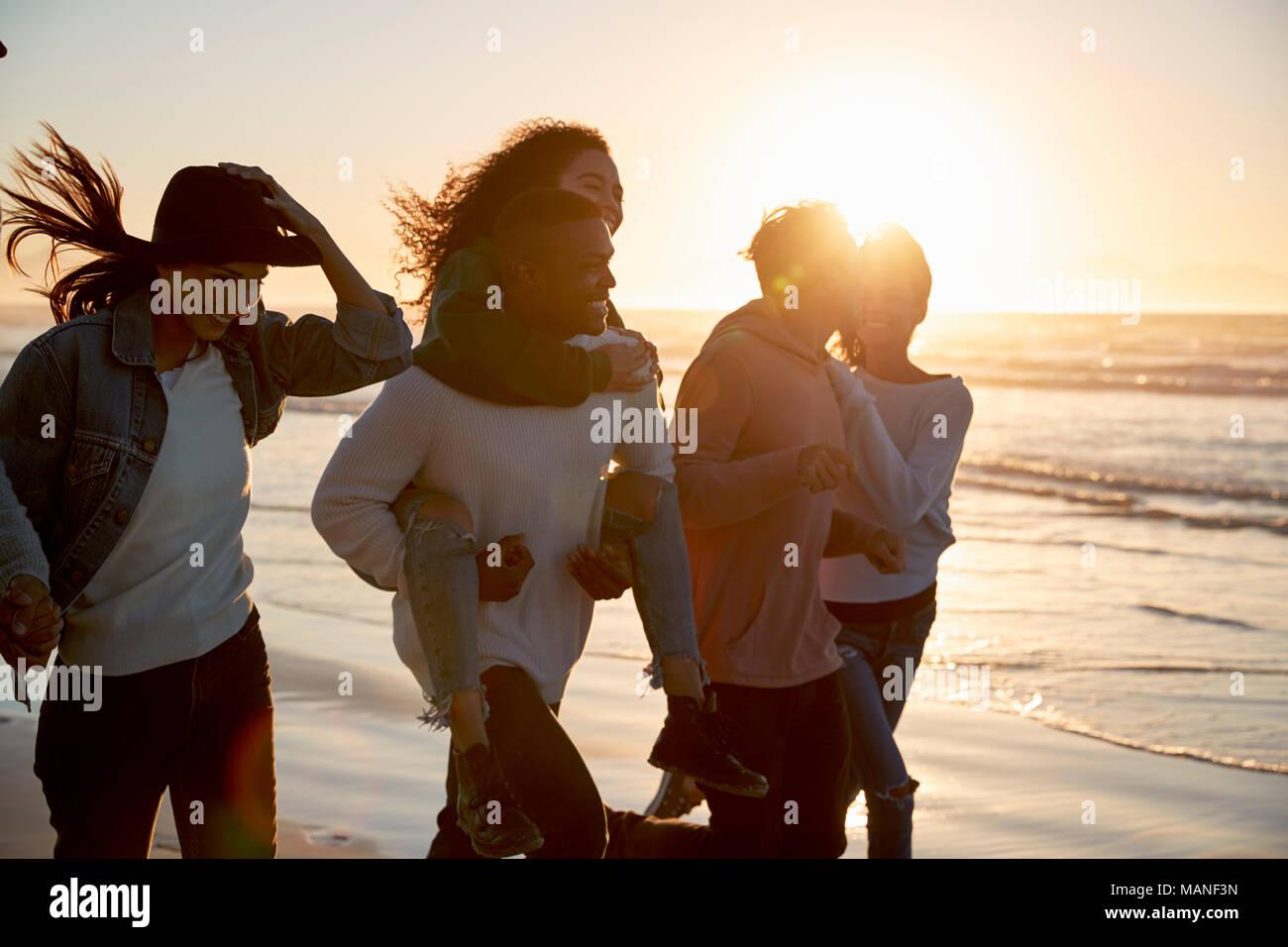 Grupo de Amigos divirtiéndose en funcionamiento a lo largo de la playa de invierno juntos Foto de stock