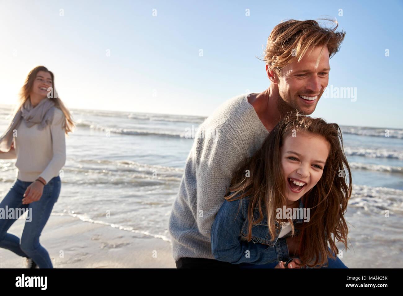 Los padres con la hija de divertirse en invierno junto en la playa Imagen De Stock