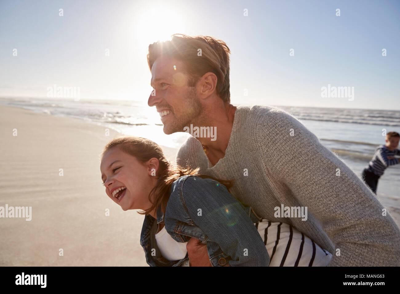 El padre con la hija de divertirse en invierno junto en la playa Imagen De Stock