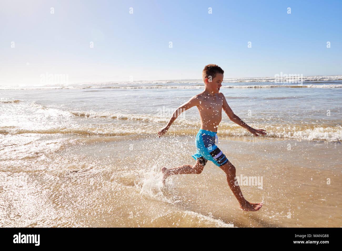 Boy en vacaciones de verano funcionan a través de ondas Imagen De Stock
