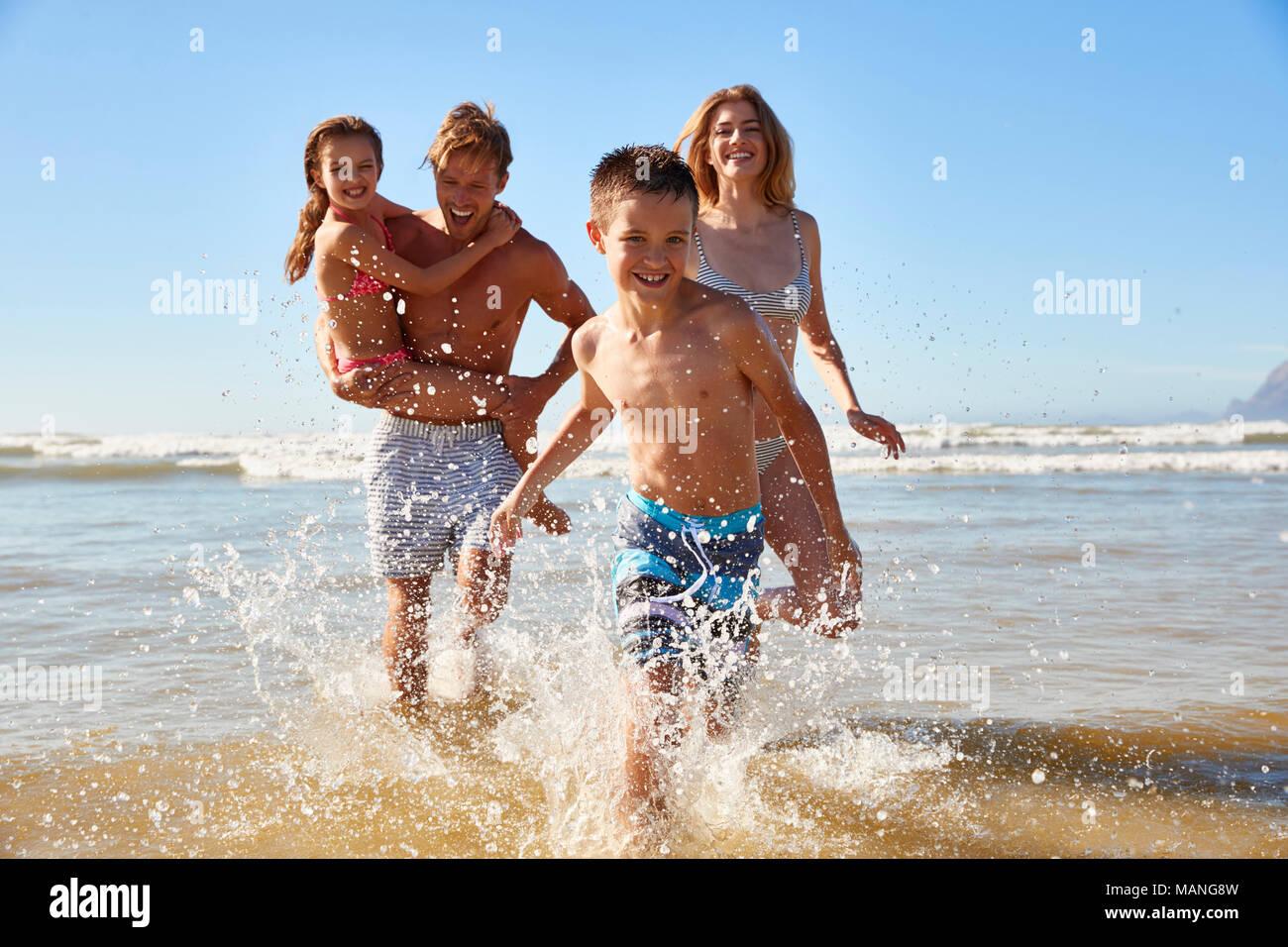 Familia de vacaciones en la playa en verano ejecutar fuera del mar hacia la cámara Imagen De Stock