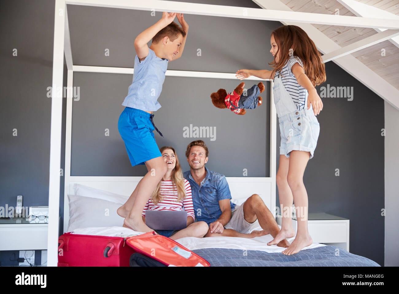 Niños entusiasmados saltar en la cama como padres Pack para vacaciones Imagen De Stock