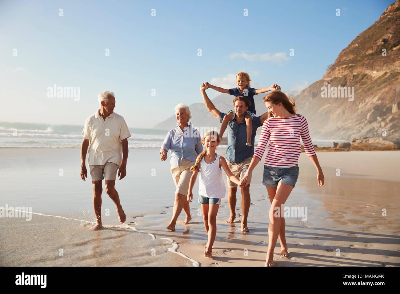 Generación de múltiples familias de vacaciones junto a la playa caminando juntos Imagen De Stock