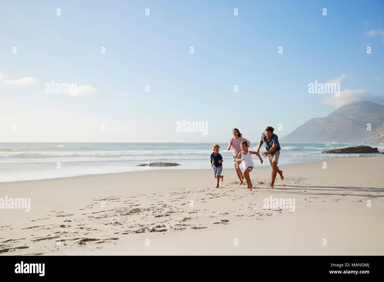 Los padres que corre a lo largo de la playa con los niños en las vacaciones de verano Imagen De Stock