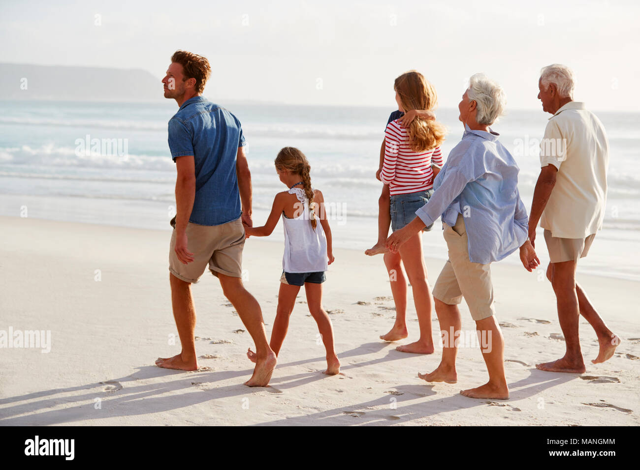 Generación de múltiples familias de vacaciones junto a la playa caminando juntos Foto de stock