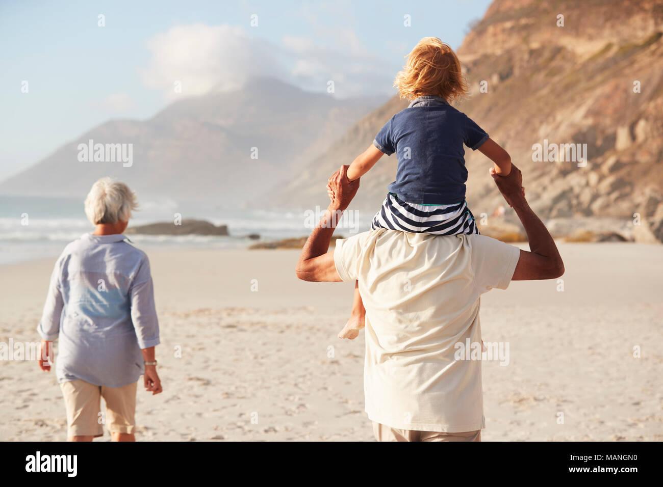 Los abuelos llevando a hombros nieto en caminar a lo largo de playa Imagen De Stock