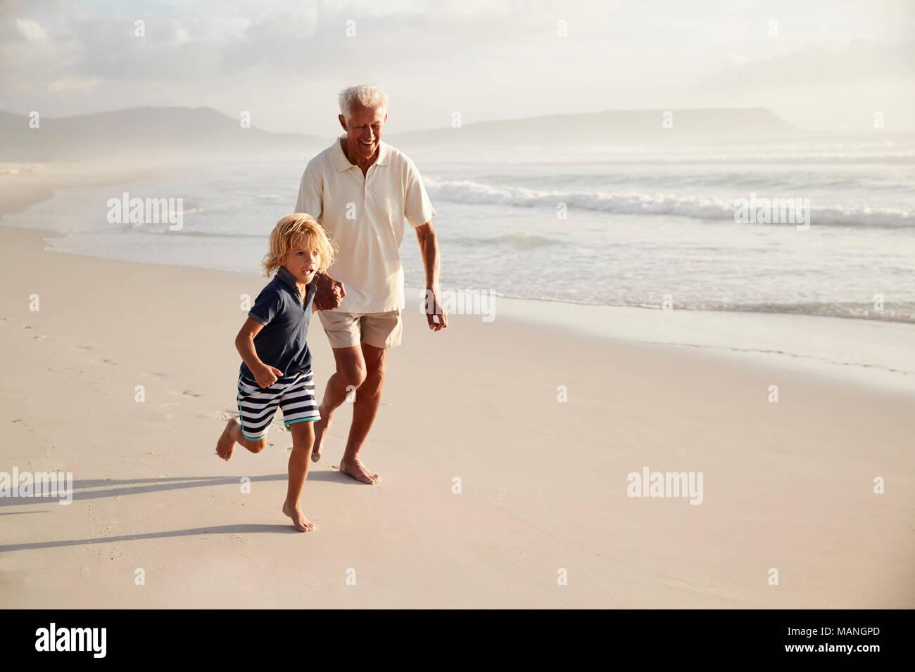 El abuelo que corre a lo largo de la playa, con su nieto en las vacaciones de verano Foto de stock