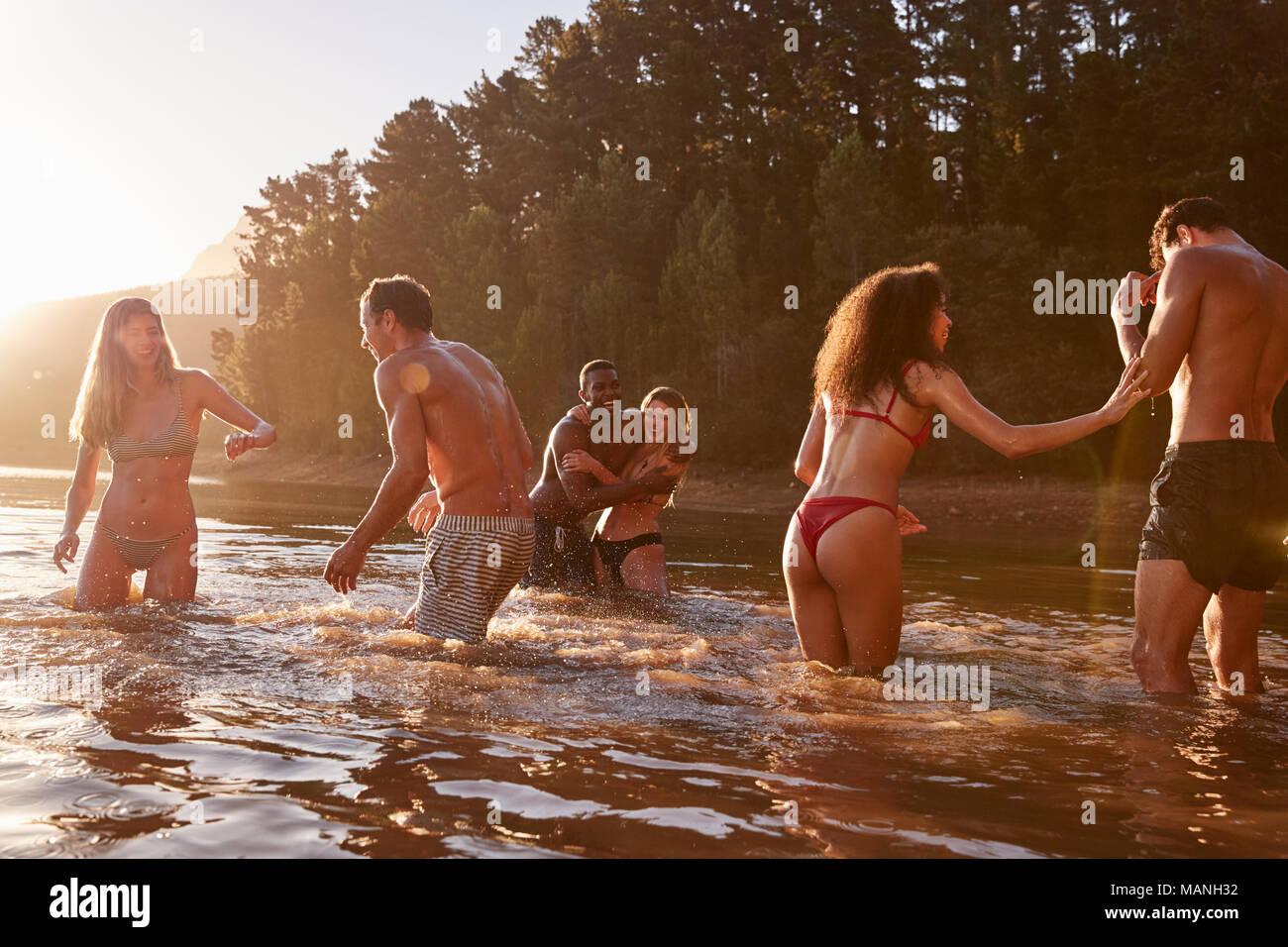 Adultos jóvenes amigos de vacaciones jugando en un lago Imagen De Stock