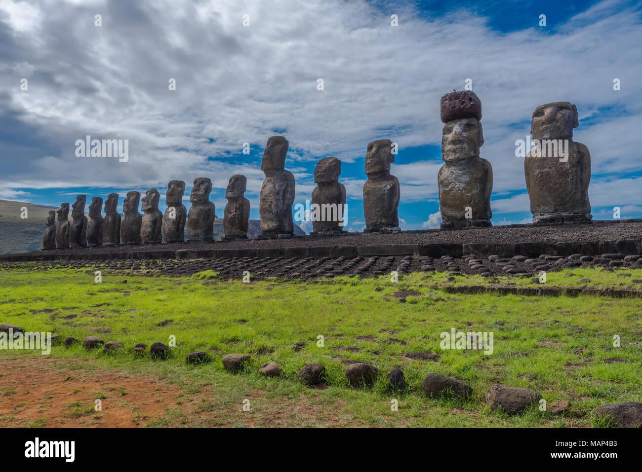 Amplio ángulo de disparo de 15 estatuas moai mirando hacia adentro a lo largo de la Isla de Pascua en Tongariki con una espectacular nube blanca y el cielo azul de fondo. Imagen De Stock