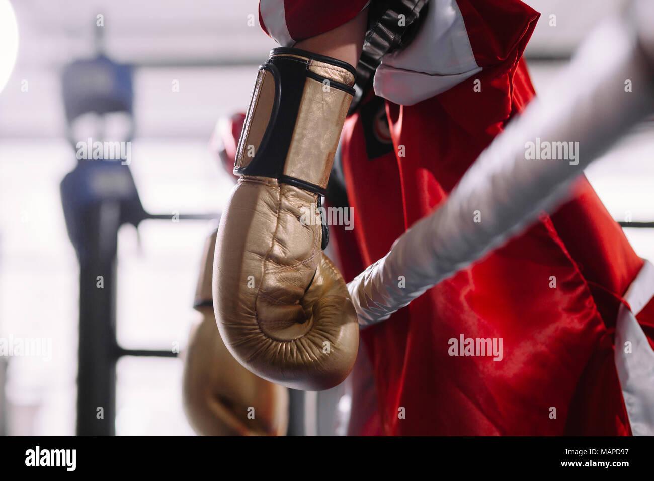 Golpeado boxeador en amarillo Guantes boxeo inclinándose sobre cuerdas Imagen De Stock