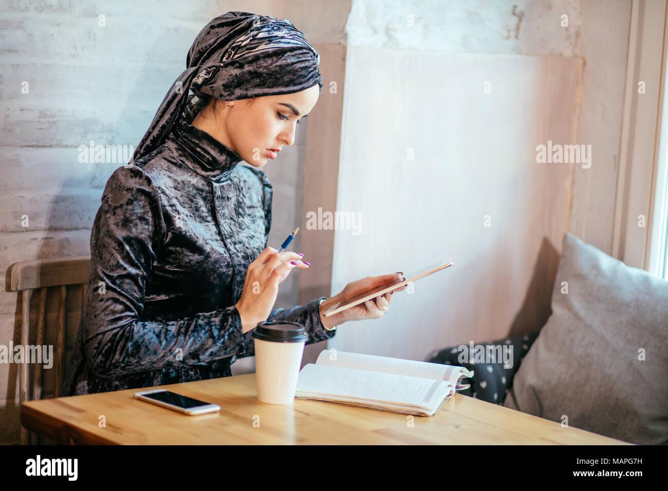 Las mujeres musulmanas que trabajan con Tablet y tomar un café en la cafetería Imagen De Stock