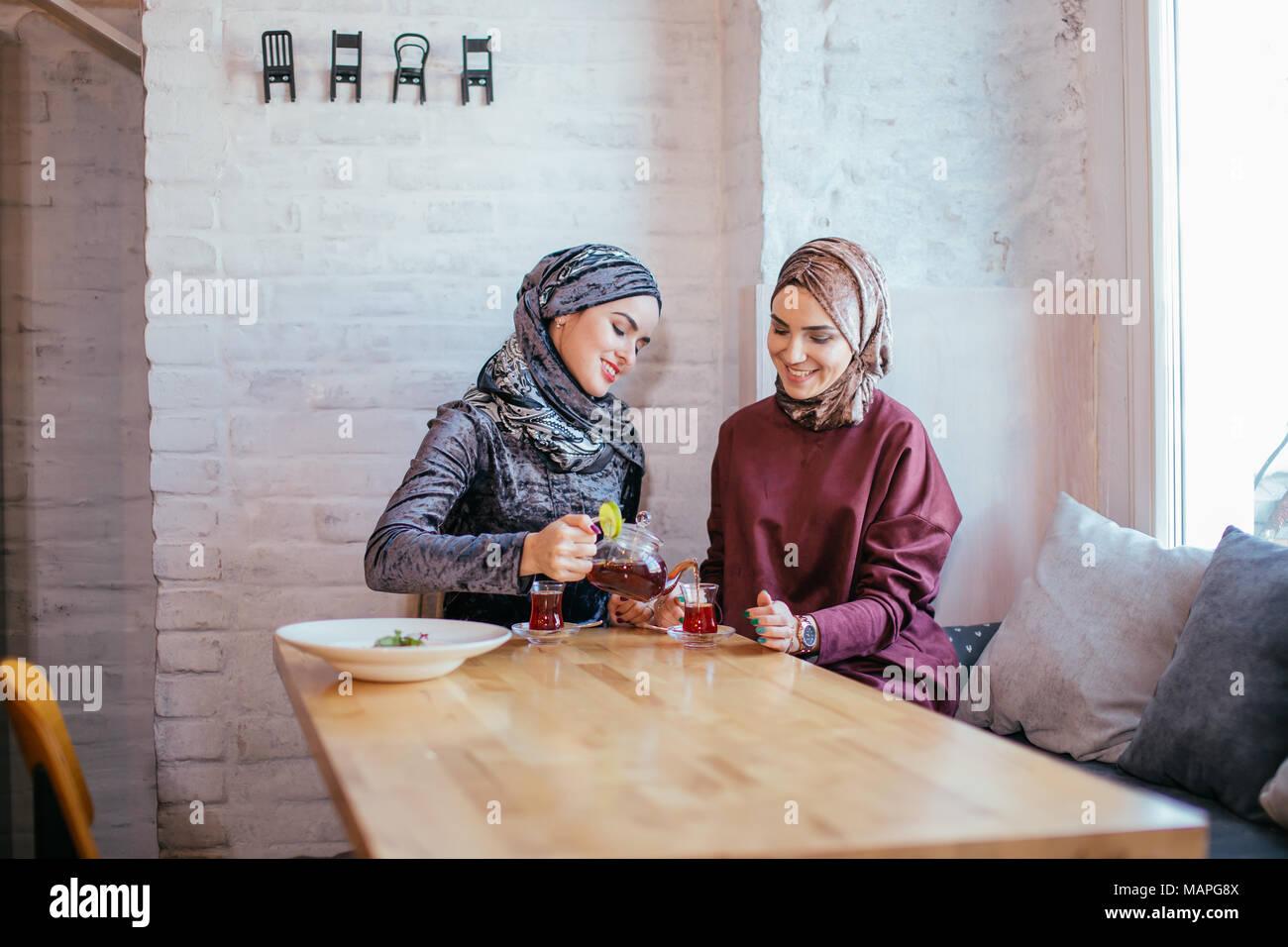 Dos mujeres musulmanas del Cáucaso beber té en el café Imagen De Stock