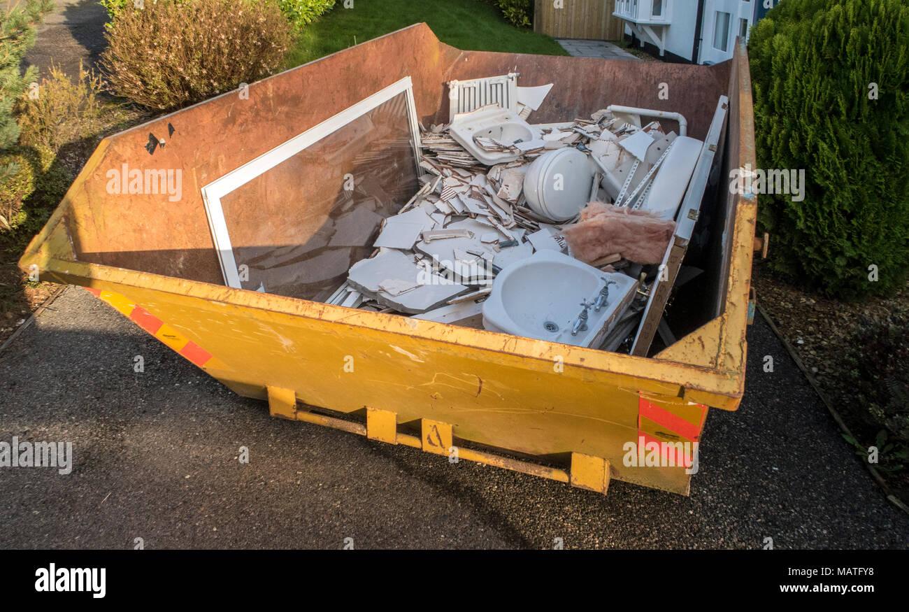Basura skip en el callejón sin salida de una casa llena de escombros de renovar un cuarto de baño Imagen De Stock