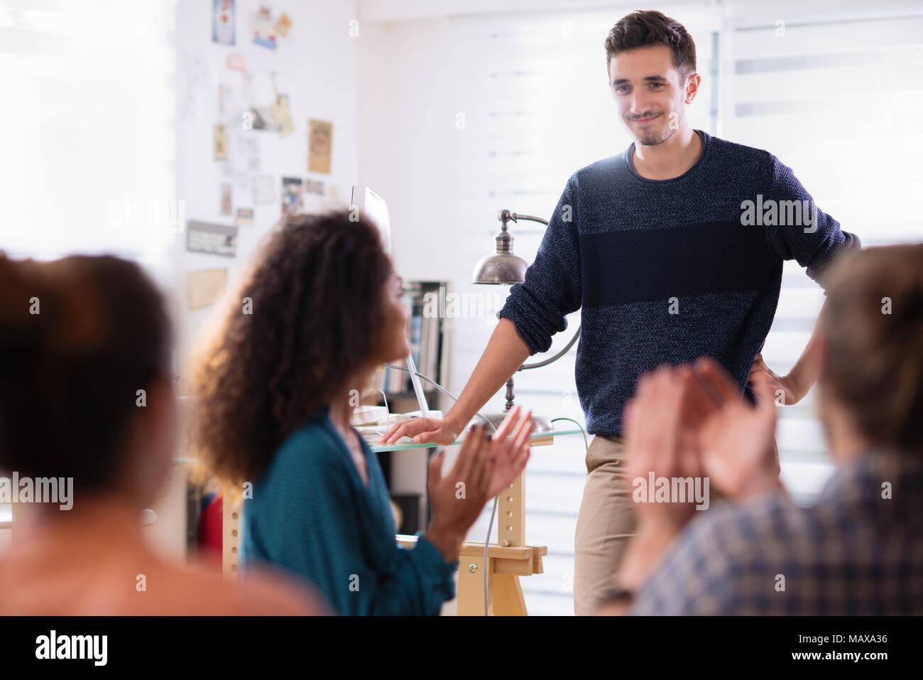 En la reunión. Un hombre joven presentando su proyecto. Él es aplaudido Foto de stock
