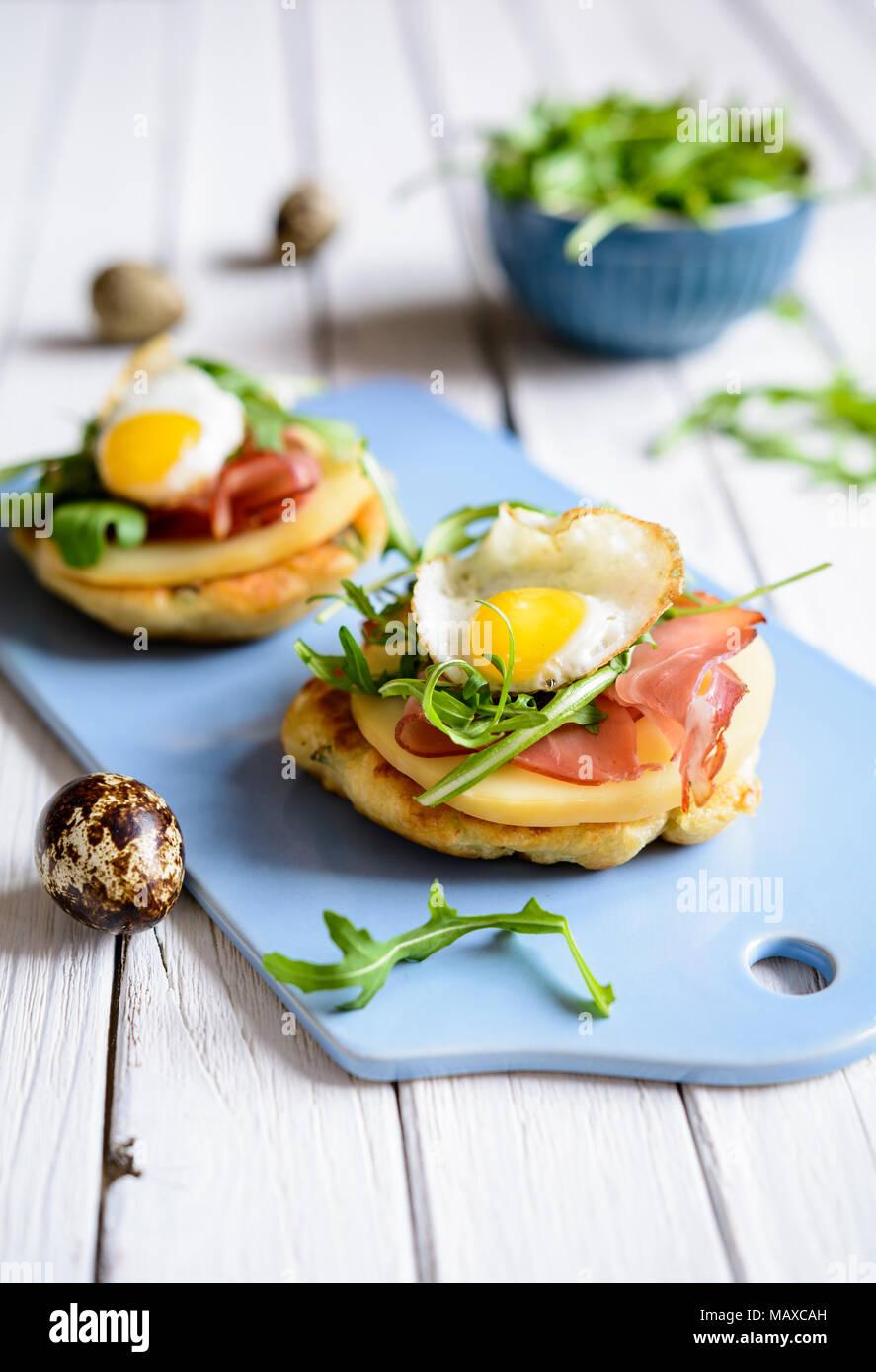 El yogur y el cebollino crepes salados con Black Forrest jamón, rebanadas de queso ahumado, huevo de codorniz y arugula Imagen De Stock