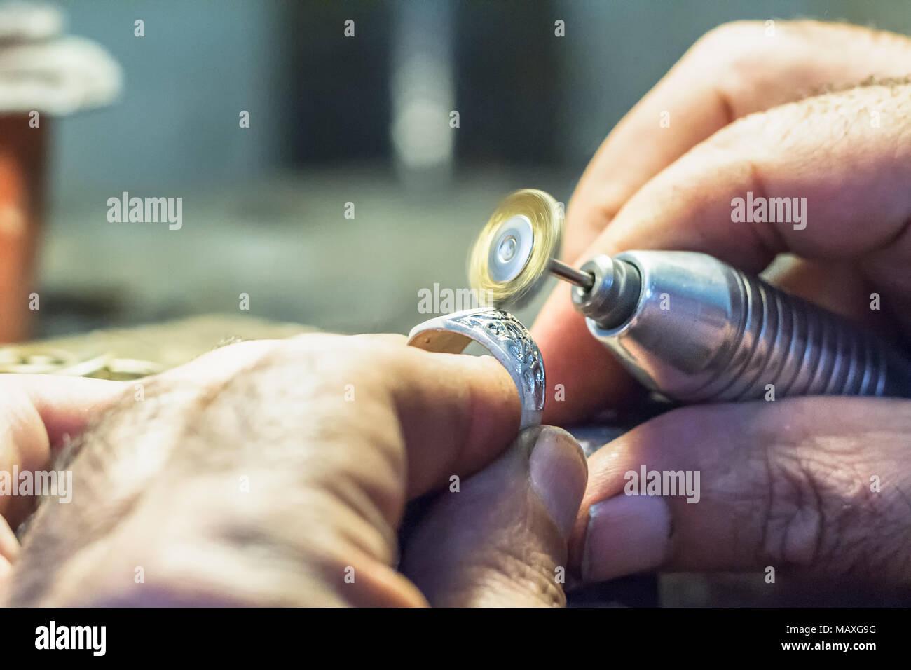 c98822e34223 Joyero masculino pulir un anillo de plata con un cepillo de alambre de  cobre montado sobre