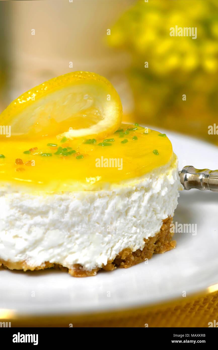 Restaurante de lujo de un mousse de limón cheesecake una horquilla de plata sobre una placa blanca de fondo suave con flores amarillas y una copia del anuncio espacio Imagen De Stock