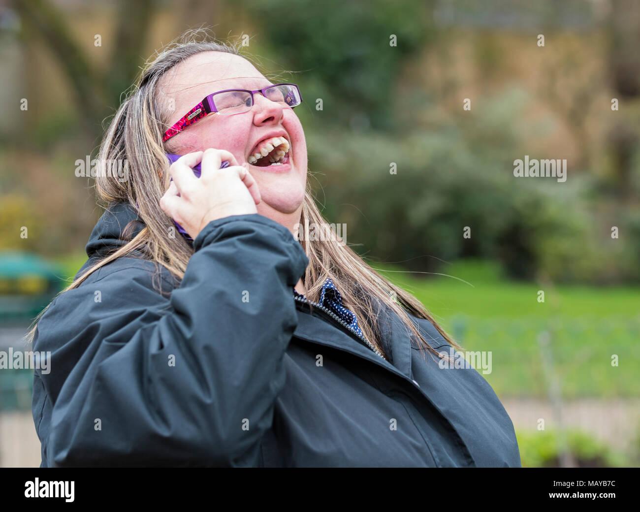 Mujer joven riendo y mirando feliz mientras disfruta de una conversación telefónica con un amigo. Concepto de felicidad. Tener una risa. Riendo con los amigos. Imagen De Stock