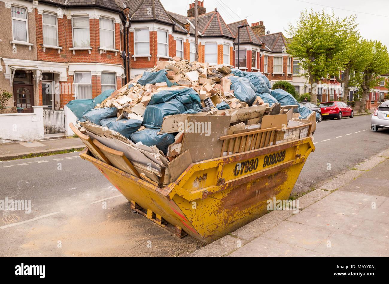Builder's escombros en plena saltar en una calle de casas adosadas, Haringey, al norte de Londres, Reino Unido Imagen De Stock