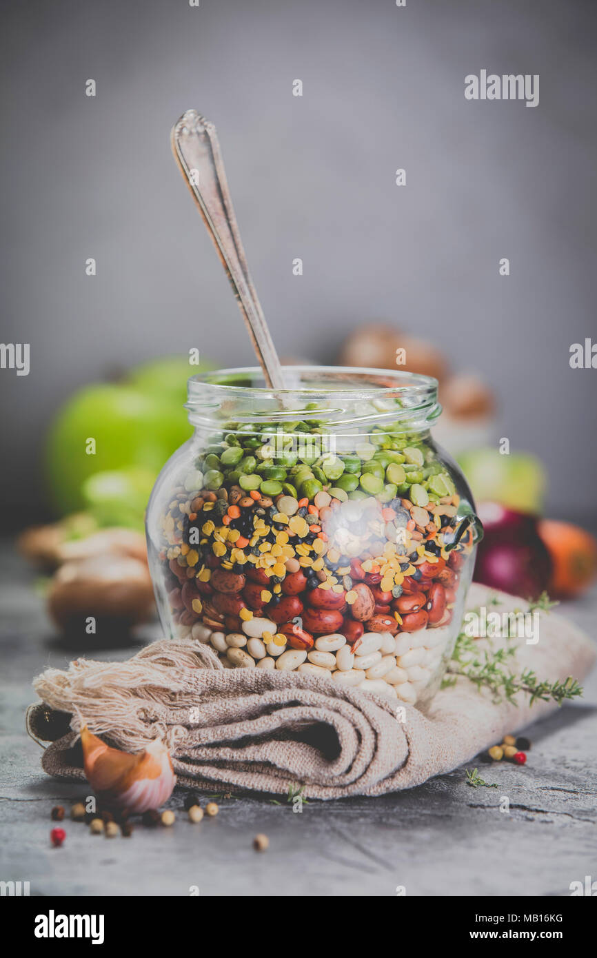 Legumbres: lentejas, garbanzos, frijoles arvejas verdes en un frasco de vidrio y las verduras crudas. Fuente de proteínas vegetarianas. Concepto de comida vegetariana y saludable Imagen De Stock