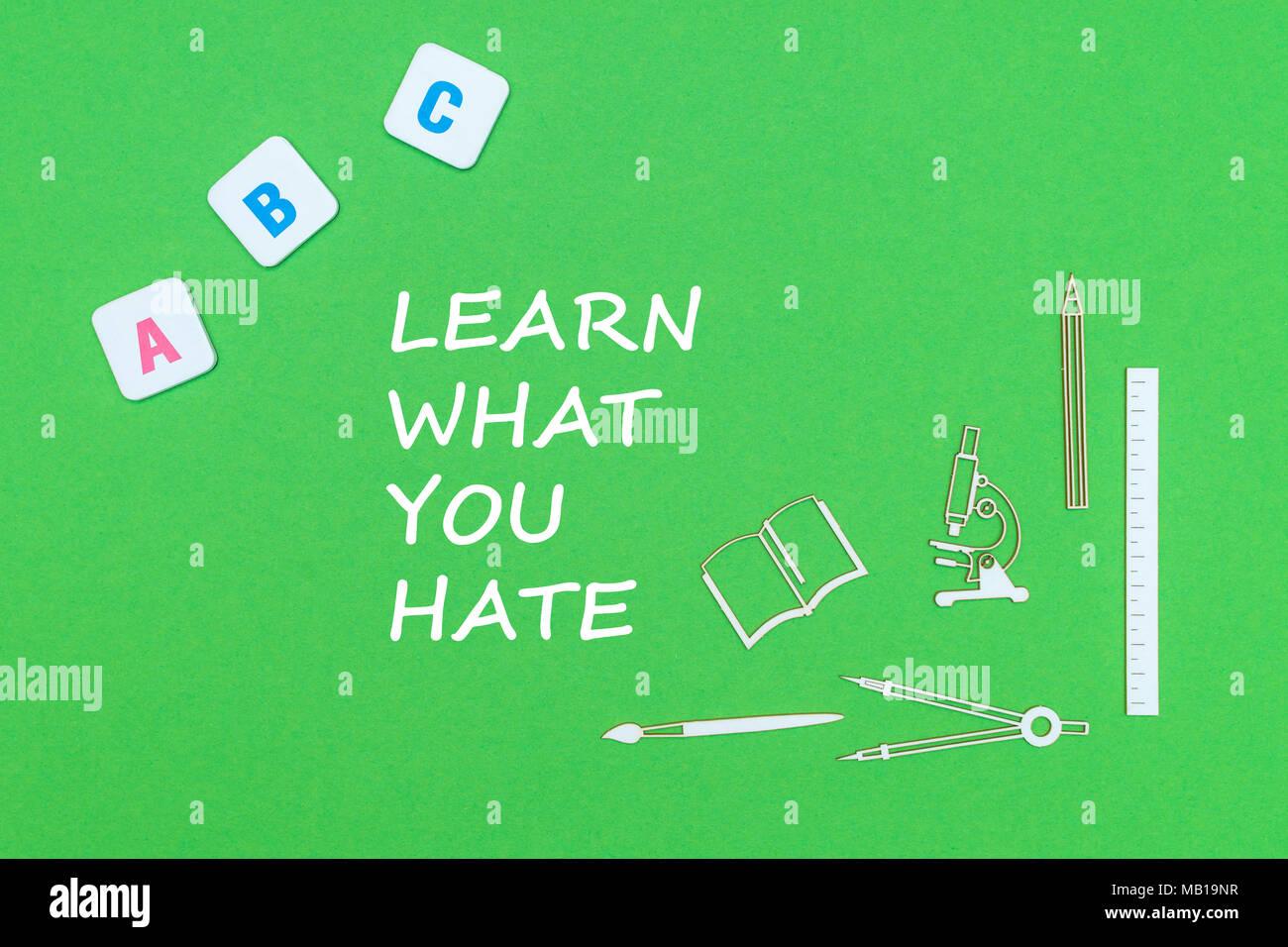 Concepto de texto escolar, aprender qué te odio, suministros escolares, abc minitures madera letras en tablero verde Imagen De Stock
