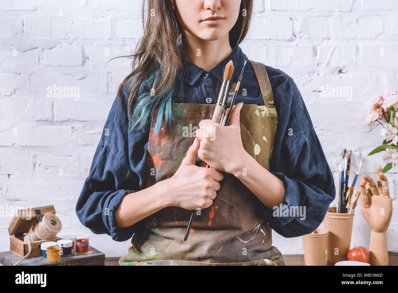 Imagen recortada de artista femenina que sujetan las escobillas Imagen De Stock