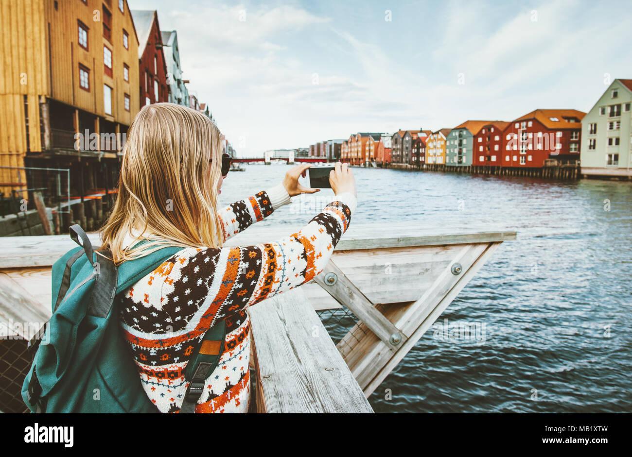 Mujer turista tomando fotos por smartphone en Noruega turismo vacaciones en el estilo de vida al aire libre coloridas casas escandinavas hitos de la ciudad de Trondheim arch Imagen De Stock