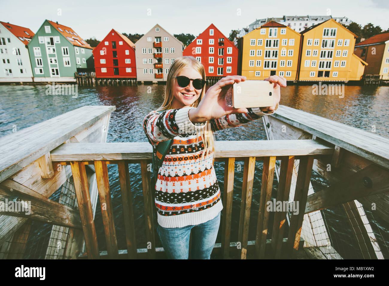 Mujer sonriente tomando selfie feliz viajando en la ciudad de Trondheim, Noruega vacaciones de fin de semana de la moda en el estilo de vida al aire libre alberga monumentos archit escandinavo Foto de stock