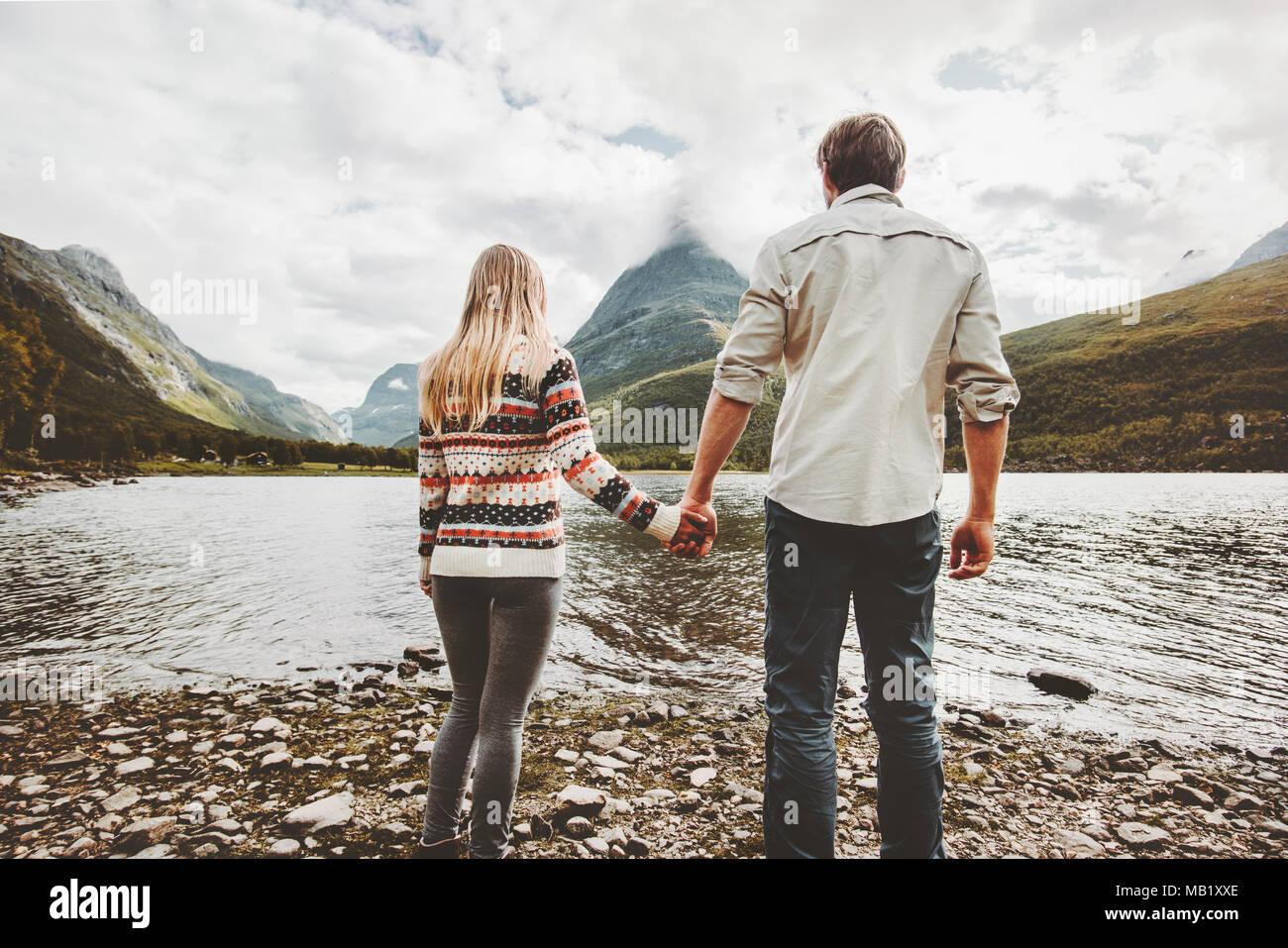 Par el hombre y la mujer tomados de la mano disfrutando de las montañas y el lago ver familia viajando juntos de aventuras al aire libre vacaciones en concepto de estilo de vida Imagen De Stock