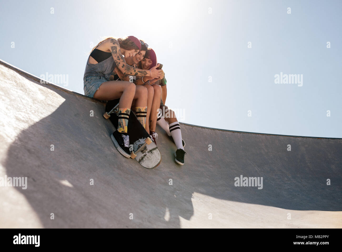 Grupo de mujeres a través de teléfono móvil en el parque de skate.  Patinadores femenino 36c7794d3c9