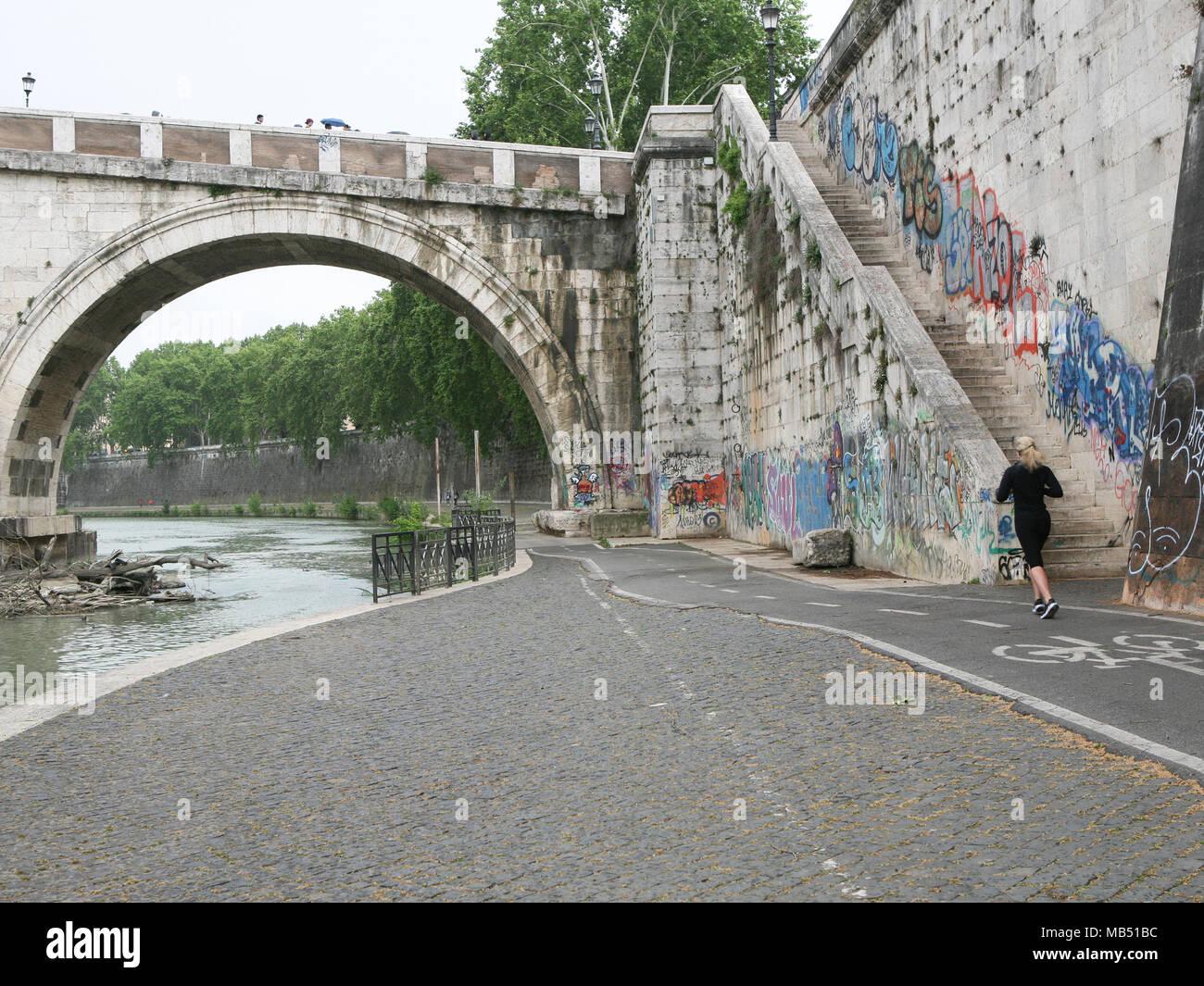 La mujer que se ejecutan en el carril bici por debajo del río Tíber en puente Ponte Sisto, Roma, Italia Foto de stock