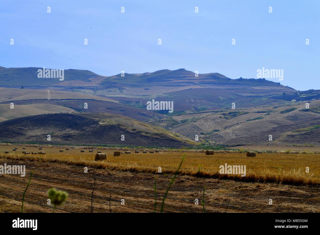 Paisaje siciliano después de la cosecha con los fardos de heno, Antecedentes, Italia Foto de stock
