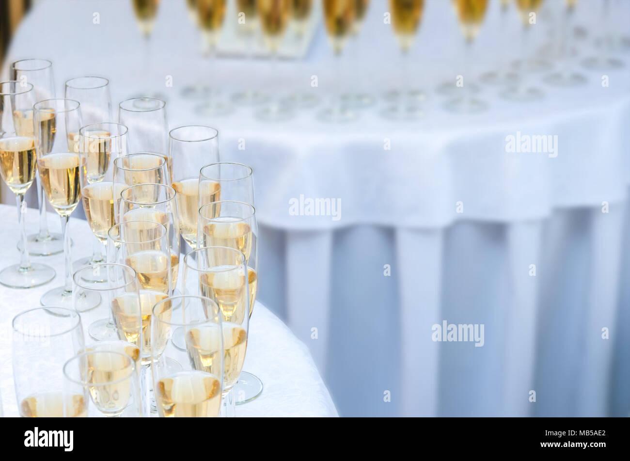Un montón de copas de vino con una botella de champán o vino blanco sobre la mesa redonda. Antecedentes de alcohol Imagen De Stock