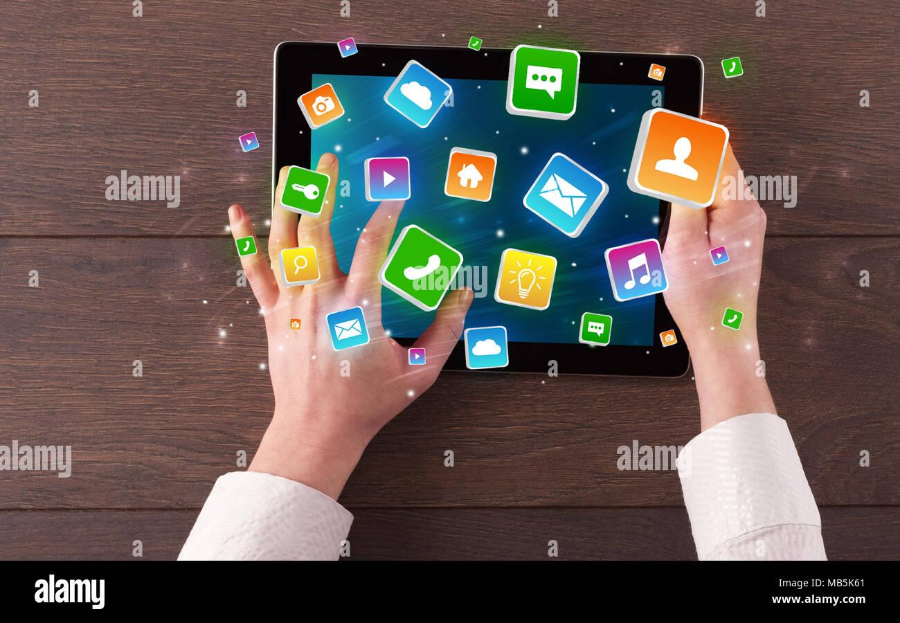 Mano con tablet con rebote colorido concepto símbolos e iconos de aplicaciones Imagen De Stock