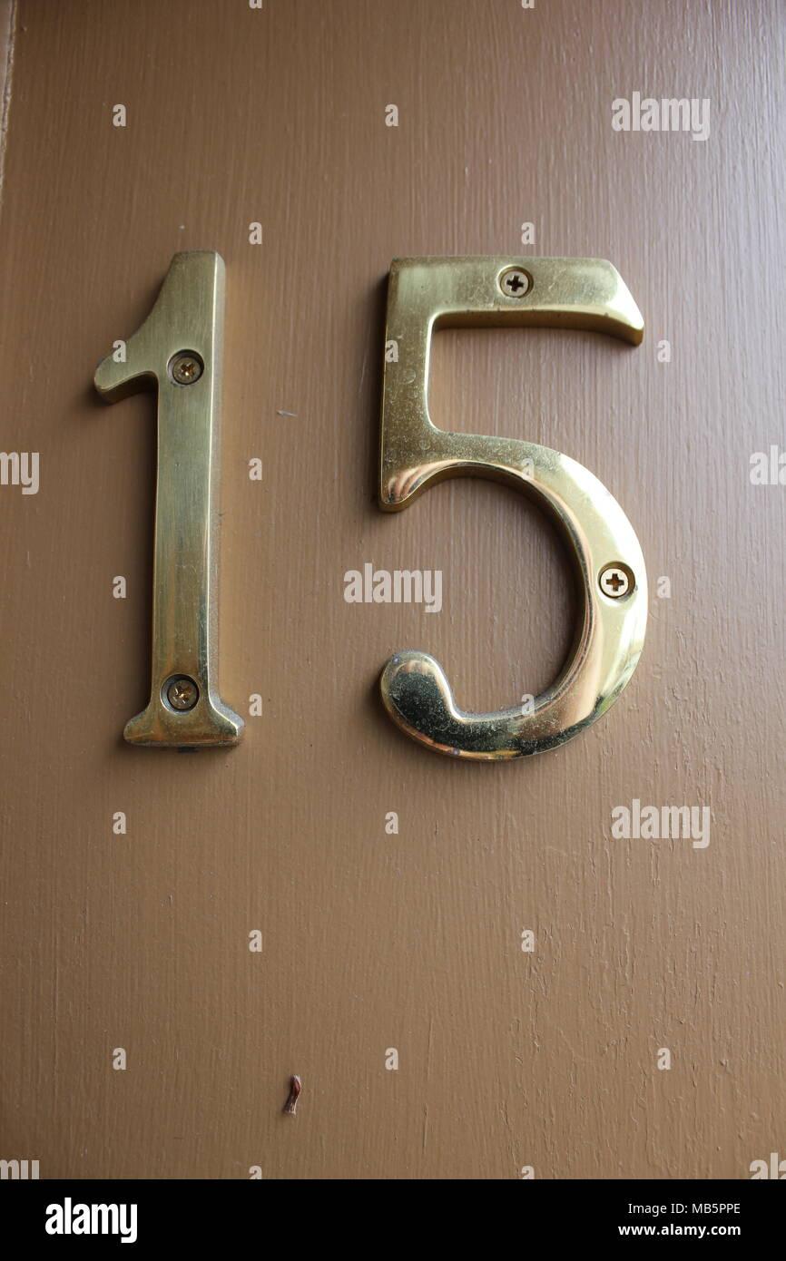 El número 15 en metal oro brillo texto letras atornillada a una pared pintada de color beige. Imagen De Stock