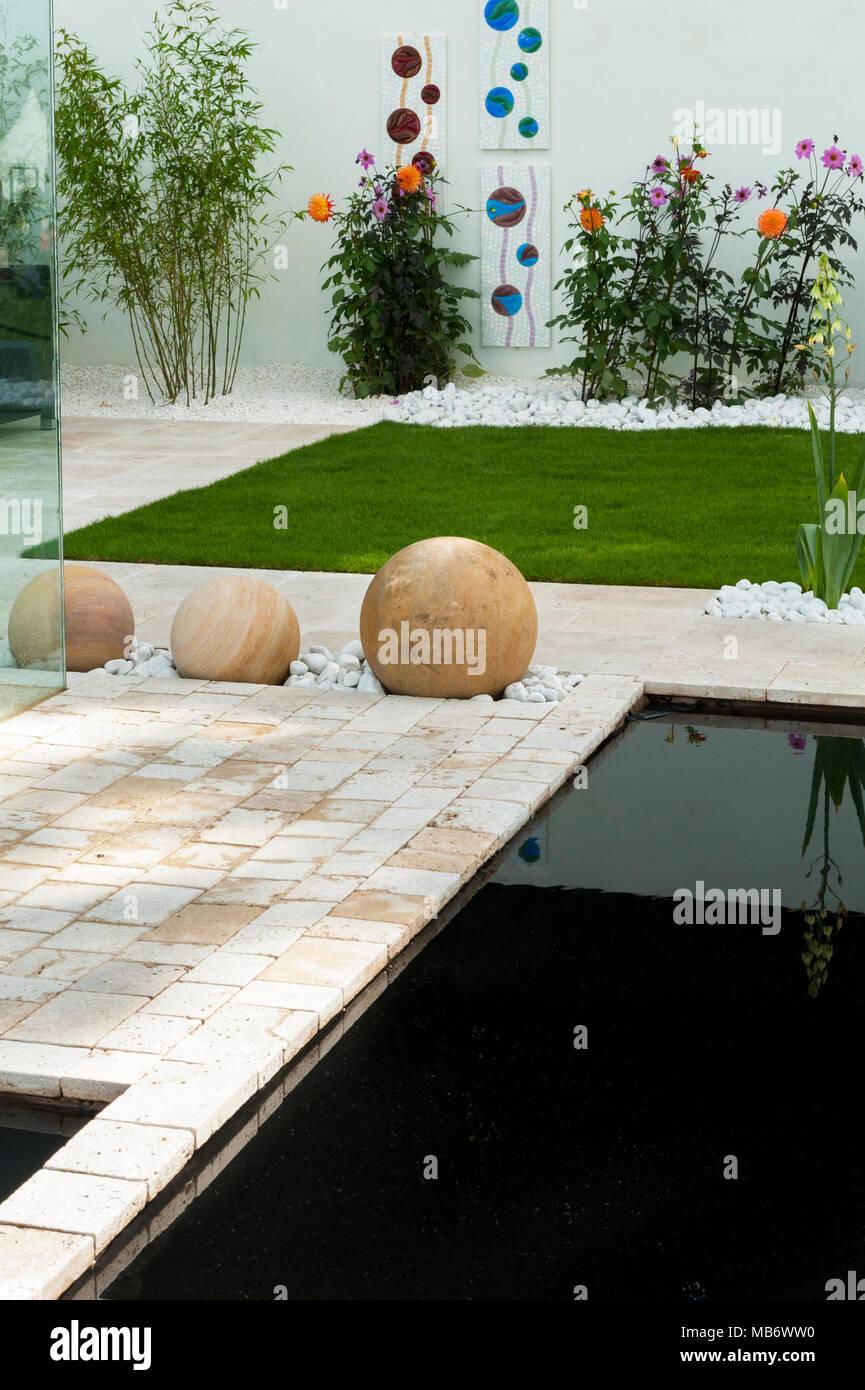 """Contemporáneo y minimalista, """"respirar"""" show garden con elegante patio, paredes blancas, un estanque y esferas de piedra - RHS Flower Show, Tatton Park, Inglaterra, Reino Unido. Foto de stock"""
