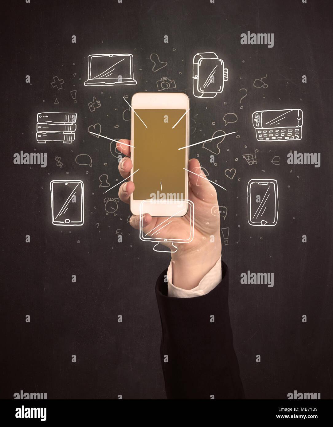 Mano del Cáucaso en traje de negocios sosteniendo un smartphone con iconos dibujados a mano Imagen De Stock
